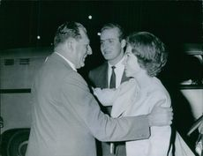 Count of Barcelona Infante Juan is affectionate to his daughter in law Queen Sofia, while his son Juan Carlos of Spain standing beside of them, both of them are smiling