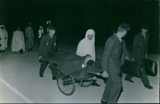 An injured man being carried on the cart by people in street.