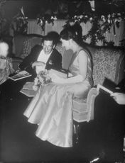 Princess Alexandra and Angus Ogilvy sitting and talking, smiling with each other.