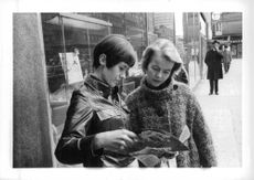 A photo of a woman reading magazine sharing to other woman in the road.