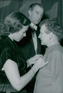 Apotekarnes Mineralvatten AB celebrates 75th anniversary. Survivor Hagander has given Mrs Karin Hård of Segerstad a medal, which is laid down by Miss Berit Sjölander