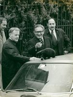 Henry Kissinger points to a black cat sitting on the roof of his car