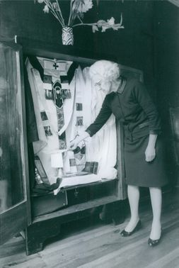 Madame Torres looking inside the cabinet with priest's clothing and things that priests use during mass.  - Aug 1968