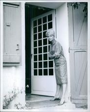 Martine Carol standing at the entrance of a house, looking at something and smiling.1960