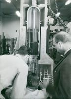 Workmaster Bo Petersson adjusts the model of the reactor for the Marviken plant
