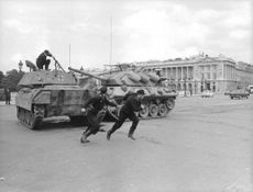 Two men, in a military uniform running to escape from a military tank behind them, in a still from a movie.