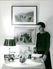 A woman standing in a room holding a photograph frame with her hand.