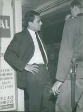 Robert Hossein standing with an officer.