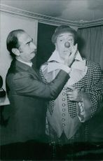 A man looking and touching Fernandel's nose. 1971.
