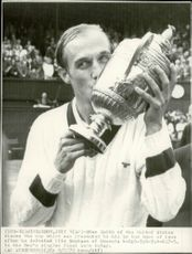 Tennis player Stan Smith picks the cup after winning the Men's Single Final at Wimbledon Station.
