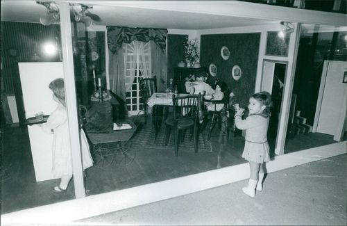 Little girl standing and looking at the display window of human size dolls, 1969.