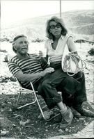 Kirk Douglas sitting with his wife on his lap looking at camera.