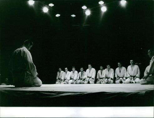 Men in Keikogi attire kneel as they attentively watch the man in front of them,  1962