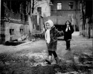 Girls play on a muddy street