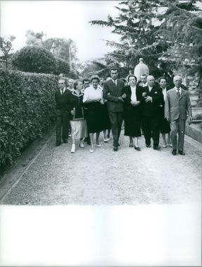 A group of men and women walking hand in had together.