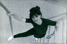 Anne Wartel hanging on ladder and looking up. Photo taken on March 24, 1966.