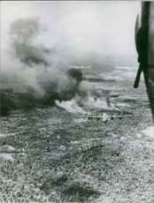 A view of an airplane spraying chemicals in the field of Vietnam.