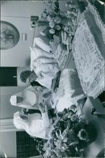 Man sitting on bed, reading the letters with the women standing beside.