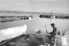 A man with a gun in Israel river, manning the area.