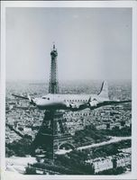 The Yanks Shove off again, A silver. C-45 Skymaster of the U.S. Army Air Forces Air Transport Command wings past the 984 foot Eiffel Tower in Paris, France