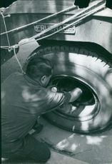 A man filling air of a truck's tire.