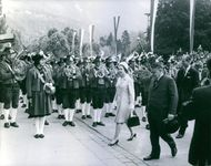 Elizabeth II passing by the street, musicians welcoming her by playing music.