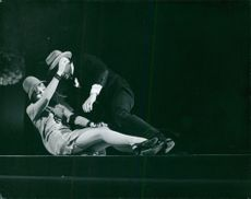 Robert Hossein and a woman falling on stage.