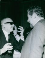 1965 A photo of an American film producer and studio executive Darryl Francis Zanuck  talking to man during an event.