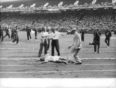Injured player during a running race, 1959.