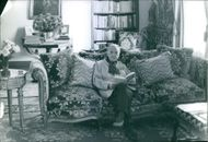 British novelist and short story writer W. Somerset Maugham have sat on the sofa and looking towards the camera while reading a book