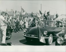 Ahmed Ben Bella standing in a car and waving at the crowd.  Taken on 16 July 1962