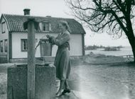 Woman retrieves water from a well