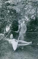 Marie-France Boyer laying on a hammock, a man looking down at her. 1967.