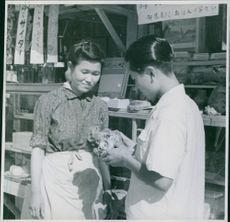Man holding something in his hands and looking at it, woman standing beside smiling at him.