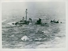 A destroyer, which appears to be half submerged, is only caught in the trough of an exceptionally high sea in the Pacific.  Taken - Jun 1945