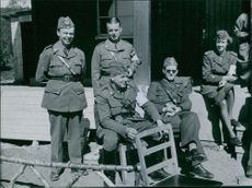 Soldiers standing and sitting together.