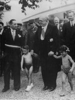 Vincent Auriol holding hand of childrens dressed in swimtrunks.