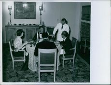 William Maugham having a meal with two men and a woman.