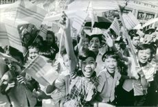 Children with flags, screaming on road.