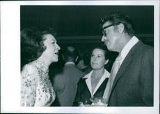 Jeane L. Dixon talking to a man and a woman.