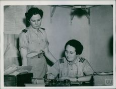 Two women soldiers communicating and while working.