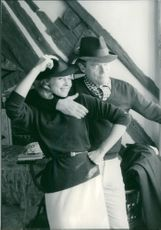 Eddie Constantine with a woman both wearing hat.