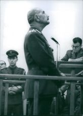 Year ?  A side view photo of Chief witness for the prosecution in the trial of 28 Greek Army officers belonging to the Aspida organization which is accused of plotting to overthrow the Government and sieze power in Greece General Grivas addressing.
