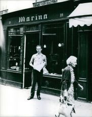 Prince Andre de Bourbon-Parme standing in front of 'Marina' shop. 1964.