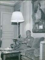 Gil Delamare siting on thre couch while reading a newspaper.