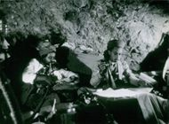 Two Yemenis writing and reading inside a cave.  - Nov 1963