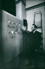Man standing in the control room, operating machine.1962