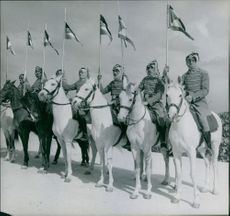 Men on horses, holding flags.
