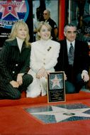 "Sharon Stone poses in front of her star on the ""Hollywood Walk of Fame"" along with actress Faye Dunaway and director Martin Scorsese"