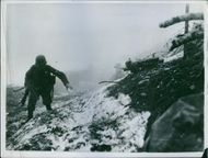 View of a soldier walking on a snowy cliff during wartime.